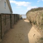 side of house and sandy path to beach